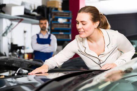 Sonriente mujer elegante admirando su coche después de repintar en el servicio automático Foto de archivo