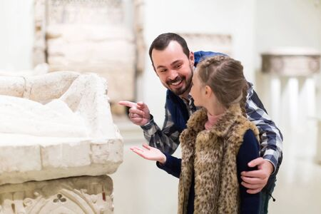 positive father and daughter looking at ancient bas-reliefs in museum
