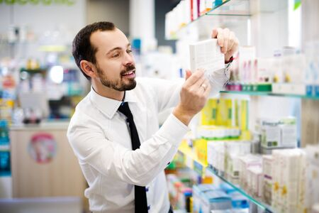 Smiling adult male customer searching for reliable drug in pharmacy