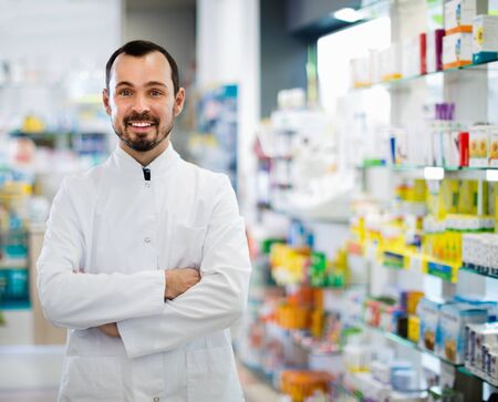 Smiling  cheerful positive male pharmacist demonstrating assortment of drugs in pharmacy