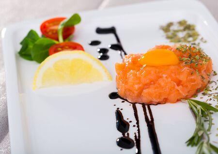 Recipe of gourmet Salmon tartare: raw salmon 200 gr, salt, black pepper, olive oil, lemon, quail egg. Finely chop fish, season with salt, pepper, oil, lemon juice, garnish with yolk, herbs and balsamic