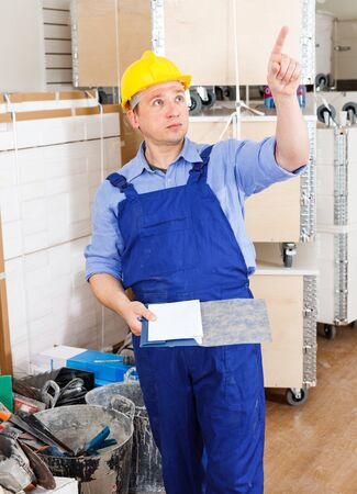 Focused construction worker inspecting room and planning upcoming repairs