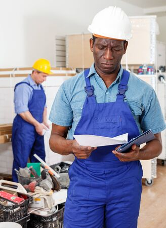 Focused African-American contractor reading building documents at construction site indoors