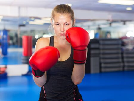 Portrait of young woman boxer in red boxing gloves training in gym