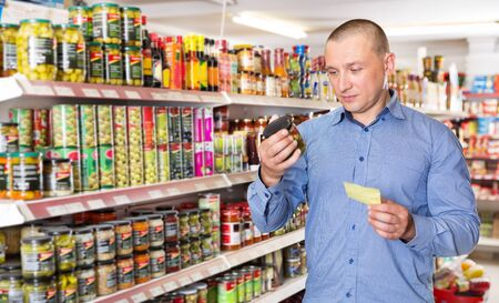 Man holding shopping list while choosing fresh products at food store