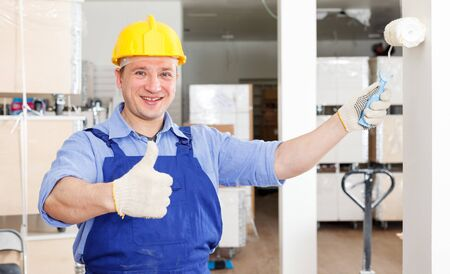 Happy professional construction worker painting wall in repairable room, giving thumbs up