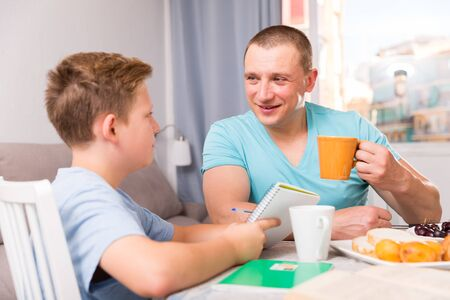Man with his adult son are reading book together for homework at the home. 版權商用圖片