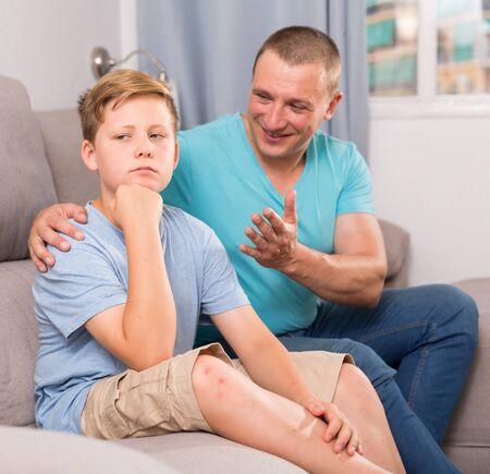 Der erwachsene Mann bittet seinen traurigen Sohn nach einem Konflikt zu Hause um Vergebung. Standard-Bild