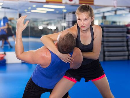 Young female exercise fight with man trainer on the self-defense course in gym