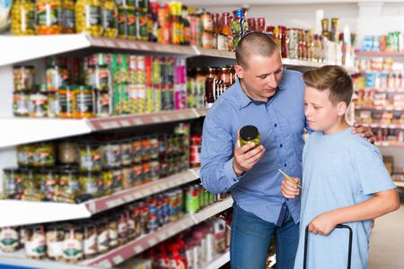 Father doing shopping with preteen boy looking at shopping list while choosing fresh products in food store