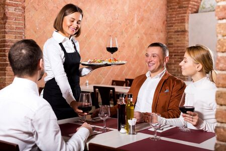 Happy young waitress placing order in front of guests in country restaurant