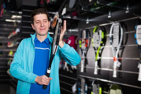 young male in uniform is holding new rocket for tennis in the store. Reklamní fotografie - 133850823