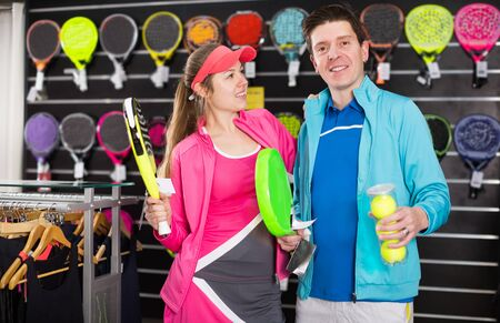 Woman and man are choosing padel racket in sportive store. Focus on both persons Reklamní fotografie