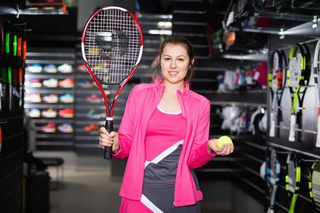 Sporty  positive glad female is demonstraiting new rocket and ball for tennis in the store.