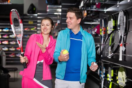 Tennis couple in sportwear is looking on modern rocket and ball for tennis at store. Focus on both persons Reklamní fotografie