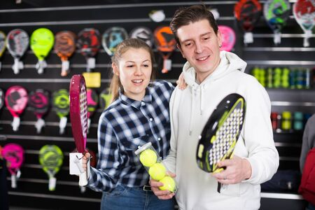 Positive couple are choosing padel racket and balls in the sportive store