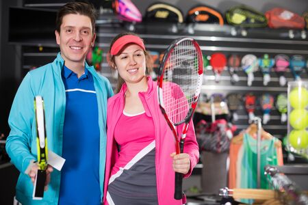 Sporty couple in uniform is demonstraiting modern racket for tennis and padel in the store.