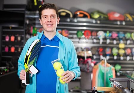 Man is standing in uniform with new padel rocket and balls in the speciality shop