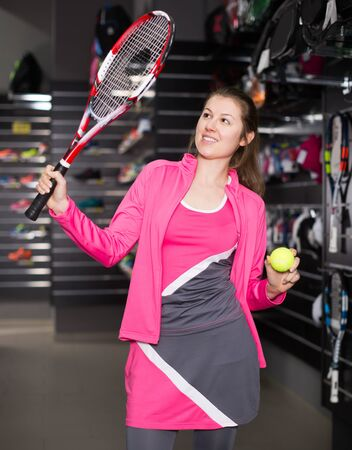 Young sportswoman is standing with new racket and ball for tennis in the speciality store. Reklamní fotografie