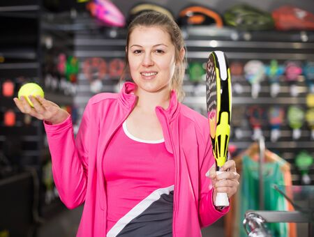 Sporty woman in uniform is holding new rocket and ball for padel in the store Reklamní fotografie