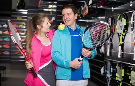 Girl and male in uniform are choosing tennis rocket and ball in the sportive store Reklamní fotografie