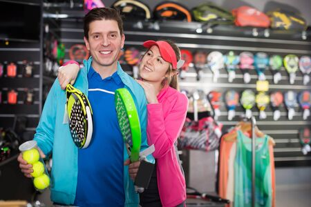 Woman and man are choosing padel racket and balls in the sportive store
