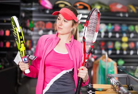 glad active female is standing in uniform with new rockets for tennis and padel in the speciality store.