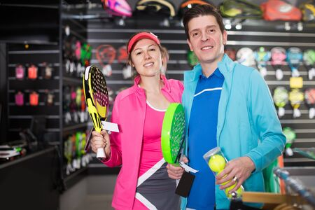 Female and man are choosing padel racket and balls in the sportive store