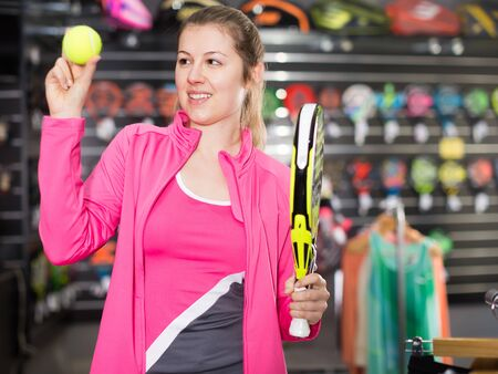 Modern woman in uniform is holding new rocket and ball for padel in the store