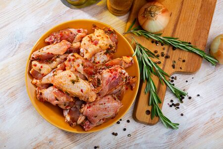 Plate with spicy marinated chicken wings prepared for family picnic on table with condiments and onions Reklamní fotografie