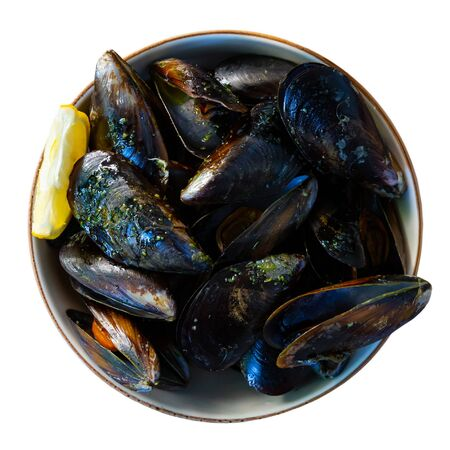 Tasty steamed mussels served with green sauce and lemon. Isolated over white background