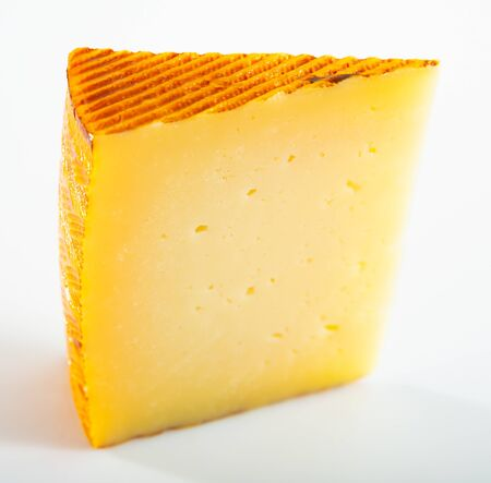 Slice of artisanal semi-hard cow milk cheese on white background