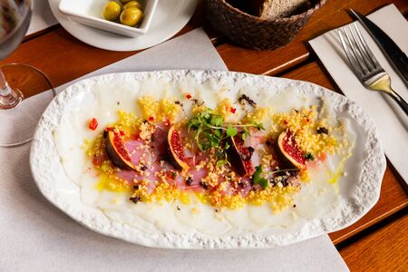 Tasty fish dish – cod carpaccio with fresh figs on plate