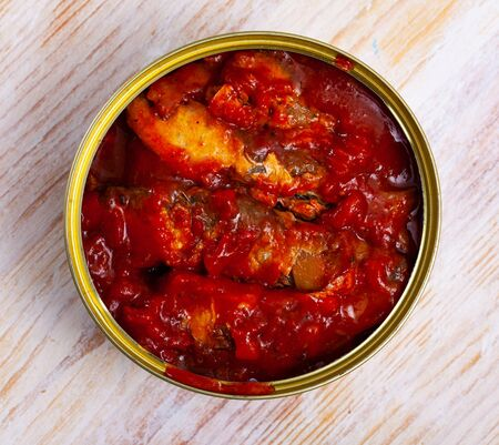 Canned sprat in tomato sauce served on wooden table