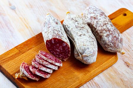 Traditional italian dry cured sausage Salamini italiani alla cacciatora on wooden table Stock Photo