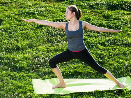 smiling irish  girl exercising on mat in morning outdoor