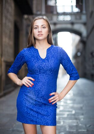 Cheerful female is playfully posing in blue dress on the street outdoor.