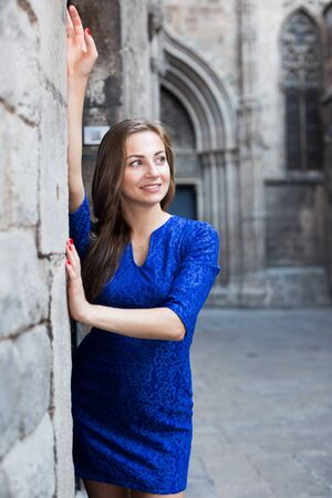 Young woman is posing in blue dress near old wall in city. Фото со стока