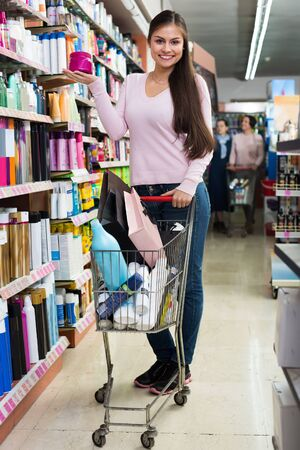 Gay young woman pushing shopping trolley in beauty department 스톡 콘텐츠