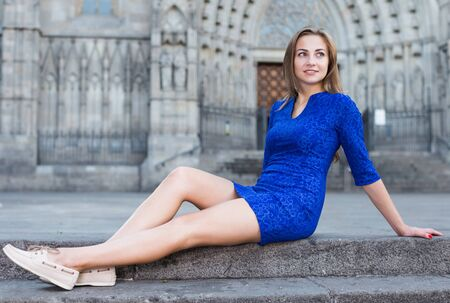 Young woman is posing sitting in blue dress in old city. Фото со стока