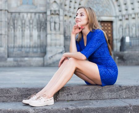 Cheerful female is playfully posing sitting in blue dress on the stairs outdoor. Фото со стока