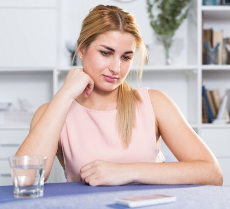 Sad woman is sitting at the table alone and upset at home.