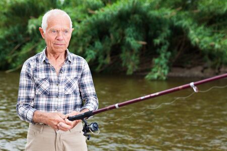 Cheerful adult fisherman standing with angling rod and fishing at sunny summer day Reklamní fotografie