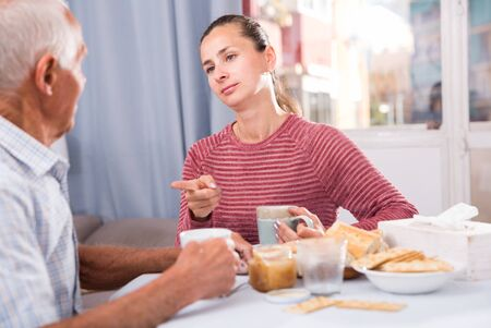 Mature male talking with young sad daughter at table with food, daughter pointing to mistakes