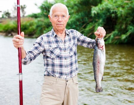 Senior caucasian fisherman satisfied with fishing holding large trout in hand Reklamní fotografie