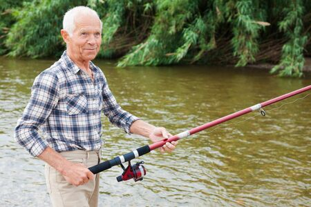 Portrait of mature man standing and fishing at river beach on summer day Reklamní fotografie