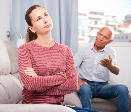 Elderly father and adult daughter quarrelling in domestic interior Banco de Imagens