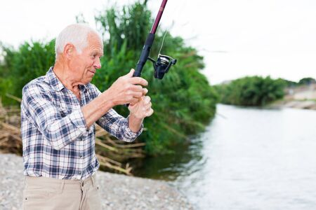 Positive adult man with rod relaxing and enjoying fishing by lakeside Reklamní fotografie