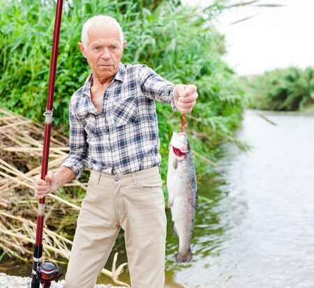 Portrait of positive senior man holding fishing tackle and catch fish on hook at riverside