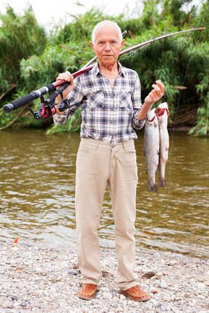 Happy elderly fisherman posing at riverside with two fresh catch trouts Reklamní fotografie